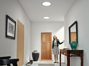 woman standing in hallway of home, looking up at sky tunnels